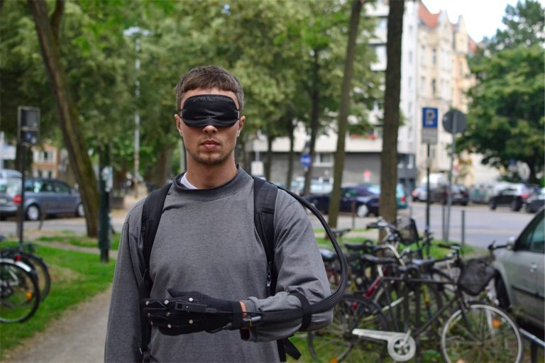 A blindfolded person is wearing the prototype on a footpath